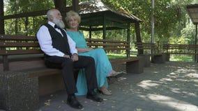 Όμορφος ηληκιωμένος και όμορφη ηλικιωμένη γυναίκα που στηρίζονται στον πάγκο στο πάρκο απόθεμα βίντεο