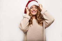 Όμορφος θετικός ξανθός σε ένα πουλόβερ και μια εορταστική ΚΑΠ Στοκ Εικόνα