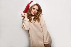 Όμορφος θετικός ξανθός σε ένα πουλόβερ και μια εορταστική ΚΑΠ Στοκ Φωτογραφίες