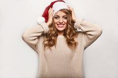 Όμορφος θετικός ξανθός σε ένα πουλόβερ και μια εορταστική ΚΑΠ Στοκ Φωτογραφία