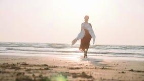Όμορφος θηλυκός άγγελος που περπατά χωρίς παπούτσια προς τη θάλασσα στο ηλιοβασίλεμα απόθεμα βίντεο