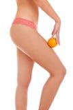 Όμορφος θηλυκός αριθμός με ένα πορτοκάλι. Στοκ Εικόνες
