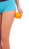 Όμορφος θηλυκός αριθμός με ένα πορτοκάλι. Στοκ Φωτογραφία