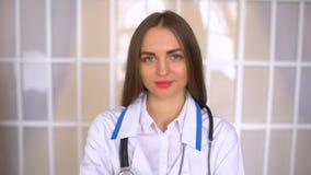 Όμορφος θηλυκός γιατρός στο άσπρο παλτό που εξετάζει τη κάμερα και που χαμογελά στεμένος με τα διασχισμένα όπλα απόθεμα βίντεο