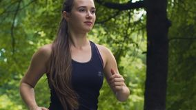 Όμορφος θηλυκός δρομέας με το μακρυμάλλες πάρκο σε αργή κίνηση, αντοχή καρδιών υγείας απόθεμα βίντεο