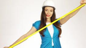 Όμορφος θηλυκός μηχανικός ή αρχιτέκτονας κατασκευής που χρησιμοποιεί την ταινία μέτρου απόθεμα βίντεο