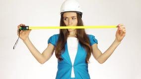 Όμορφος θηλυκός μηχανικός ή αρχιτέκτονας κατασκευής στο σκληρό καπέλο που χρησιμοποιεί την ταινία μέτρου φιλμ μικρού μήκους