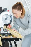 Όμορφος θηλυκός ξυλουργός που χρησιμοποιεί το κυκλικό πριόνι Στοκ εικόνα με δικαίωμα ελεύθερης χρήσης
