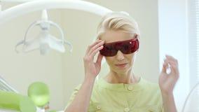 Όμορφος θηλυκός οδοντίατρος που ντύνει επάνω προστατευτικά δίοπτρα υπεριώδους τα πορτοκαλιά ασφάλειας απόθεμα βίντεο