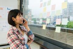 Όμορφος θηλυκός σχεδιαστής που χρησιμοποιεί το κινητό τηλέφωνο κυττάρων Στοκ Εικόνες