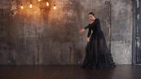 Όμορφος θηλυκός χορευτής σε ένα μακρύ μαύρο φόρεμα φιλμ μικρού μήκους