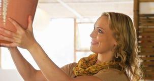 Όμορφος θηλυκός αγγειοπλάστης που ελέγχει το δοχείο απόθεμα βίντεο