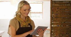 Όμορφος θηλυκός αγγειοπλάστης που χρησιμοποιεί την ψηφιακή ταμπλέτα φιλμ μικρού μήκους
