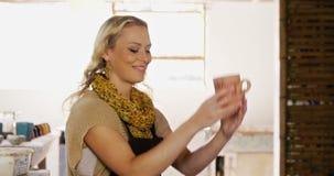 Όμορφος θηλυκός αγγειοπλάστης που χρησιμοποιεί την ψηφιακή ταμπλέτα απόθεμα βίντεο