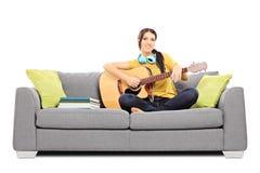 Όμορφος θηλυκός μουσικός που κάθεται σε έναν καναπέ που παίζει ένα ακουστικό γ Στοκ Φωτογραφία