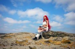 Όμορφος θηλυκός χαρακτήρας με δύο ξίφη που κάθεται σε μια πέτρα Στοκ φωτογραφία με δικαίωμα ελεύθερης χρήσης