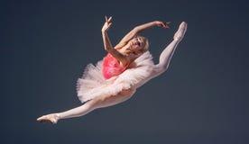 Όμορφος θηλυκός χορευτής μπαλέτου σε ένα γκρι στοκ φωτογραφίες