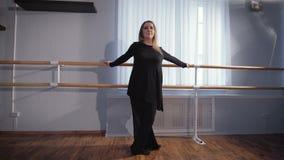 Όμορφος θηλυκός χορευτής μπαλέτου στο μαύρο κοστούμι μεταξιού που στέκεται κοντά στην μπάρα μπαλέτου στην τάξη και που κάνει το e φιλμ μικρού μήκους