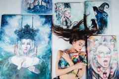 Όμορφος θηλυκός Nude καλλιτέχνης που περιβάλλεται από τον καμβά έργων ζωγραφικής στο άσπρο υπόβαθρο πατωμάτων παλέτα βουρτσών Στοκ εικόνες με δικαίωμα ελεύθερης χρήσης