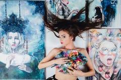 Όμορφος θηλυκός Nude καλλιτέχνης που περιβάλλεται από τον καμβά έργων ζωγραφικής στο άσπρο υπόβαθρο πατωμάτων παλέτα βουρτσών Στοκ Εικόνες