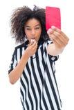 Όμορφος διαιτητής που φυσά το συριγμό της και που παρουσιάζει κόκκινη κάρτα Στοκ Φωτογραφίες