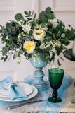 Όμορφος διακοσμήστε τον πίνακα με τα κεριά, το βάζο με τα λουλούδια και το γαμήλιο κέικ στον πίνακα στο στούντιο Στοκ εικόνα με δικαίωμα ελεύθερης χρήσης
