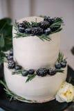 Όμορφος διακοσμήστε το γαμήλιο κέικ με τα κεριά και τα λουλούδια Στοκ Φωτογραφία