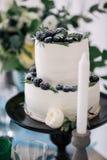 Όμορφος διακοσμήστε το γαμήλιο κέικ με τα κεριά και τα λουλούδια Στοκ Εικόνα