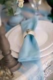 Όμορφος διακοσμήστε το γαμήλιο πιάτο με τα κεριά και τα λουλούδια στοκ φωτογραφία