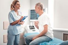 Όμορφος ιατρικός βοηθός που απολαμβάνει την επικοινωνία με τον επισκέπτη στοκ εικόνες