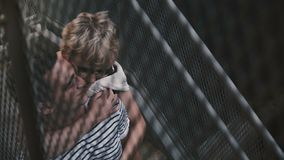 Όμορφος ισπανικός άνδρας και καυκάσια γυναίκα που στέκονται και που αγκαλιάζουν στα μεταλλικά σκαλοπάτια οδών πόλεων, άποψη μέσω  απόθεμα βίντεο