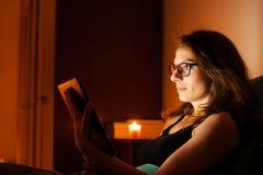 Όμορφος Ιστός σερφ γυναικών σε μια ταμπλέτα στο κρεβάτι πριν από τον ύπνο Στοκ εικόνες με δικαίωμα ελεύθερης χρήσης