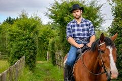 Όμορφος κάουμποϋ, αναβάτης αλόγων στη σέλα, μπότες πλατών αλόγου adn στοκ εικόνες