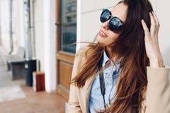 Όμορφος και νέο κορίτσι σε ένα παλτό και ένα μαντίλι και γυαλιά ηλίου που κάθονται στον πάγκο Καλοκαίρι Στοκ Εικόνες