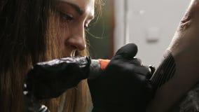 Όμορφος καυκάσιος θηλυκός καλλιτέχνης δερματοστιξιών που στρέφεται στη διαδικασία της εργασίας της φιλμ μικρού μήκους