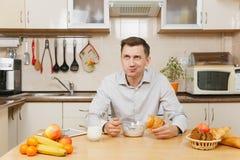 Όμορφος καυκάσιος νεαρός άνδρας, που κάθεται στον πίνακα Υγιής τρόπος ζωής casserole που μαγειρεύει την εύγευστη βασική σπιτική σ Στοκ Φωτογραφίες