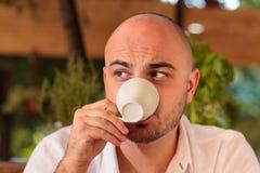 Όμορφος καφές κατανάλωσης ατόμων και κοίταγμα στην πλευρά Στοκ Εικόνες
