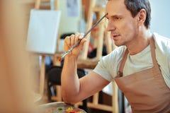 Όμορφος καλλιτέχνης που σκέφτεται με τη βούρτσα διαθέσιμη στοκ εικόνες με δικαίωμα ελεύθερης χρήσης