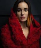 Όμορφος κόκκινος επενδύτης γυναικών με τα κόκκινα τριαντάφυλλα λουλουδιών στο στούντιο Στοκ Εικόνα