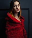 Όμορφος κόκκινος επενδύτης γυναικών με τα κόκκινα τριαντάφυλλα λουλουδιών στο στούντιο Στοκ εικόνα με δικαίωμα ελεύθερης χρήσης