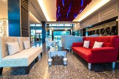 Όμορφος κόκκινος καναπές και εκλεκτής ποιότητας πίνακας στην υποδοχή Στοκ Φωτογραφίες