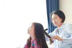 Όμορφος λίγο ασιατικό κορίτσι παιδιών με μακρυμάλλη και mom ντυμένος επάνω για την ομαλή τρίχα στο πρωί στο δωμάτιο στοκ φωτογραφίες