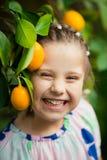 Όμορφος λίγο ευτυχές κορίτσι στο ζωηρόχρωμο φόρεμα στον κήπο Lemonarium λεμονιών που επιλέγει τα φρέσκα ώριμα λεμόνια στο καλάθι  Στοκ φωτογραφίες με δικαίωμα ελεύθερης χρήσης