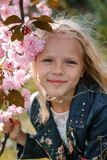 Όμορφος λίγο κορίτσι παιδιών με τα λουλούδια sakura στοκ εικόνες με δικαίωμα ελεύθερης χρήσης