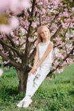 Όμορφος λίγο κορίτσι παιδιών με τα λουλούδια sakura στοκ φωτογραφίες