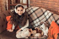 Όμορφος λίγο κορίτσι brunette με τη μακρυμάλλη συνεδρίαση σε έναν καναπέ Στοκ Εικόνες