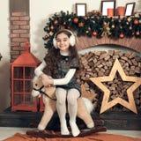 Όμορφος λίγο κορίτσι brunette με τη μακρυμάλλη συνεδρίαση σε ένα παιχνίδι χ Στοκ φωτογραφία με δικαίωμα ελεύθερης χρήσης