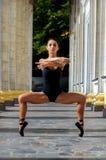 Όμορφος λεπτός χορευτής αθλητριών σε ένα μαύρο κοστούμι και pointe στοκ εικόνες