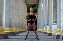 Όμορφος λεπτός χορευτής αθλητριών σε ένα μαύρο κοστούμι και pointe στοκ φωτογραφίες