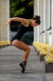 Όμορφος λεπτός χορευτής αθλητριών σε ένα μαύρο κοστούμι και pointe στοκ φωτογραφία